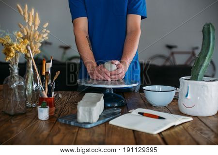 Young craftsman or artisan awaits to start his creative process in workshop studio on big wooden table with clay and work stand in front of him