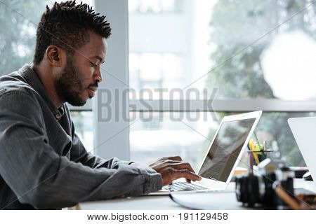 Picture of handsome thinking serious young man sitting in office coworking. Looking aside using laptop computer.