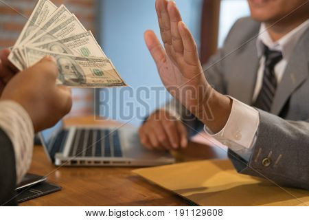 Businessman rejecting money cash banknote from a man. honest business people in suit refuse to take the bribe - anti bribery corruption venality concept.