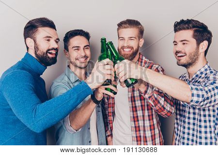 Close Up Portrait Of Four Happy Men Friends, Clinking Their Glasses Of Beer, Smiling, Alll Are In Ca