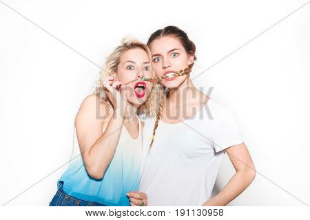 Young stylish girls making faces and grimacing while posing on white background.