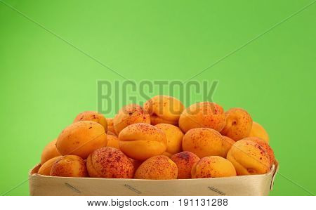 Fresh Ripe Apricots In Wooden Basket Over Green