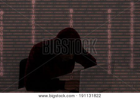 computer hacker wearing a hooded top using laptop in the dark. The man breaks the access to steal information and infect computers and systems. hacking network security identity theft and internet crime double exposure with 01 code binary number