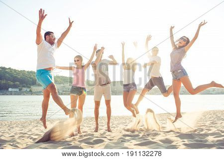 Happiness, Summer, Joy, Friendship And Fun Concept. Group Of Happy Young Cheerful Students Are Jumpi