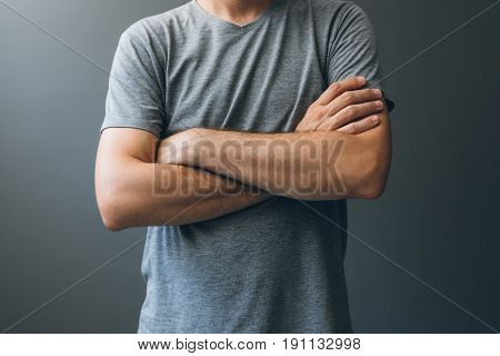 Casual adult man with arms crossed body language for stress relief masking insecurities anxiety and fear as well as self restraint or frustration