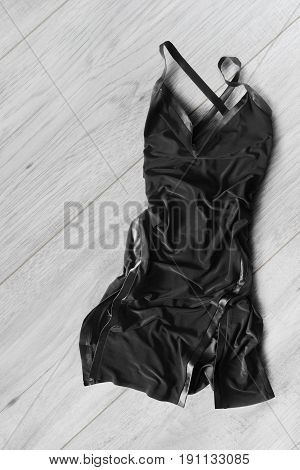 Crumpled black silk dress lying on white wooden floor
