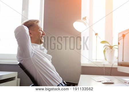 Side view of young content man sitting at desktop with computer and relaxing.