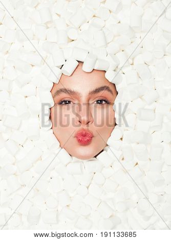 From above shot of woman lying in white marshmallows and pouting lips while looking at camera.