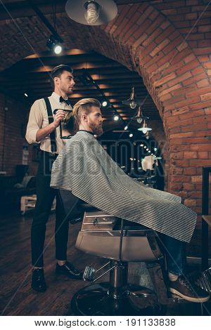 Full Length Of Handsome Classy Dressed Barber Shop Stylist, Who Is Presenting The Result Of His Styl