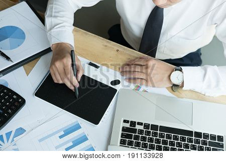 young male graphic designer working with computer. creative man using digital tablet and stylus pen at modern office. business technology design and people concept