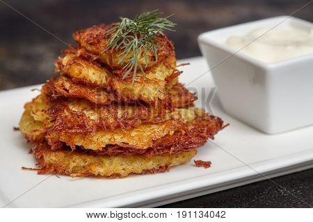 Tasty potato pancakes or latke with sauce on white plate closeup
