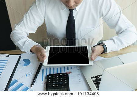 asian businessman using a digital tablet in office. young male start up entrepreneur working on touch pad at workplace