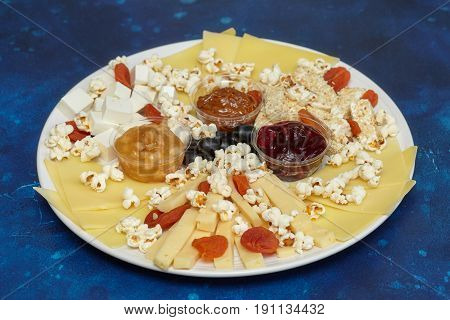 Cheese assorti with sauces and popcorn blue background