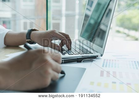 Young Graphic Designer Working With Computer And Color Swatch. Creative Man Using Stylus Pen And Dig