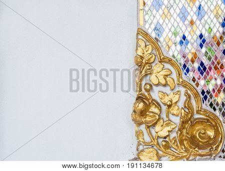 Golden floral stucco with the glass mosaic near the white wall of the Thai church.