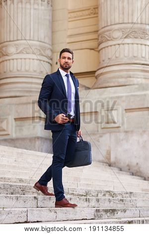 A handsome young businessman walking down on the stairs while holding his phone and his bag