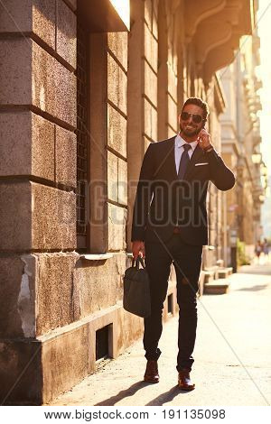 A handsome young businessman talking on his phone and walking on the street in the sunset