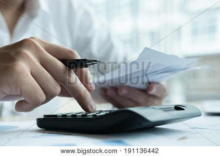 Man Calculate Domestic Bills At Home. Businessman Using Calculator At Office. Young Male Checking Ba