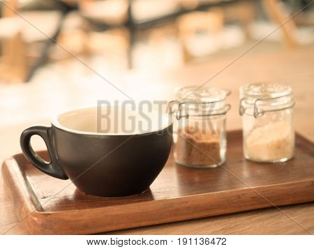 Fresh hot americano coffee in cup without topping and sugar bottle on a wooden plate on wooden table