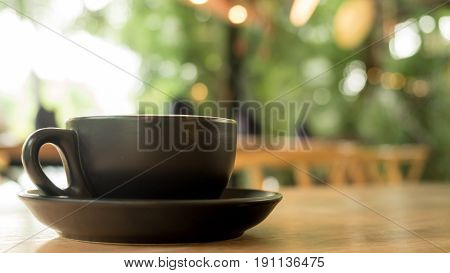 Fresh hot americano coffee in cup without topping on a wooden table with cafe shop background