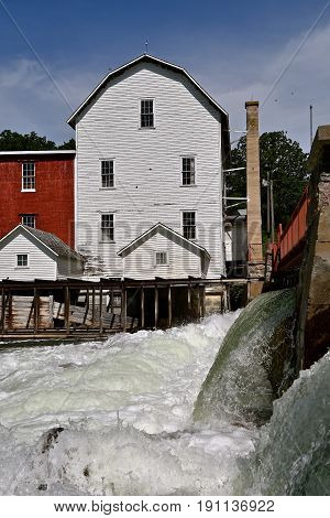 Water cascades over a dam and spillway of an old historic grist mill for grinding grain into flour.