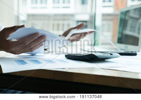 Man calculate domestic bills at home. Businessman using calculator at modern office. Young male checking balance and costs. Start up counting finance. Business people doing paperwork for paying taxes