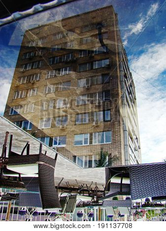 Reflection of a building in a glass surfaced table.
