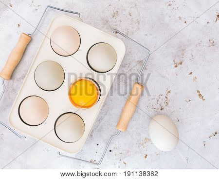 Organic chicken eggs. Farm fresh free range  chicken eggs in vintage holder on rustic background. Top view, blank space, vintage toned image