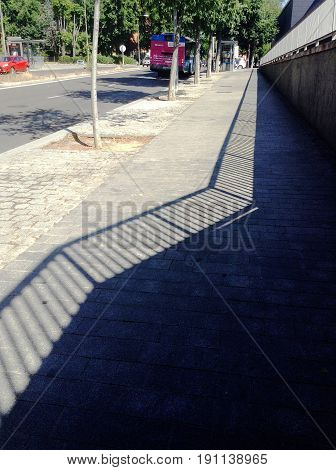 Handrail shadow on the asphalt one hot afternoon.