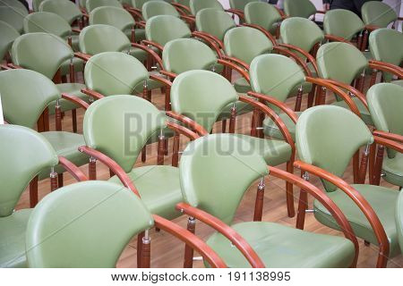 Comfortable seats in empty corporate meeting office for presentation. Group of empty the same chairs with modern backrest and green upholstery in rows at unknown auditorium