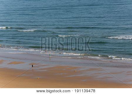 PRAIA DA ROCHA, PORTUGAL - APRIL 23, 2017: People at the famous beach of Praia da Rocha in Portimao. This beach is a part of famous tourist region of Algarve.