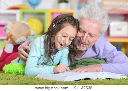 grandfather reading book with his little  grandaughter