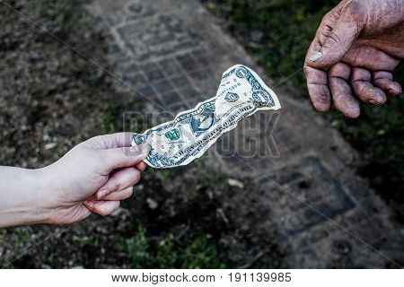 Woman giving money to a grown man. From hand to hand.