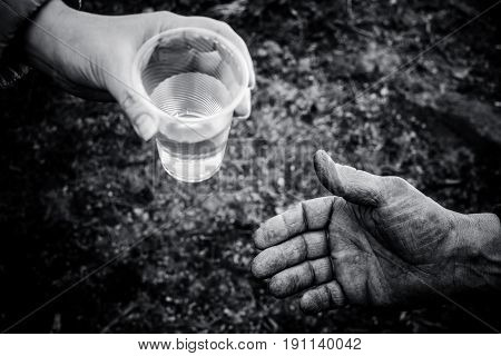 Woman giving a glass of water an adult male. From hand to hand.