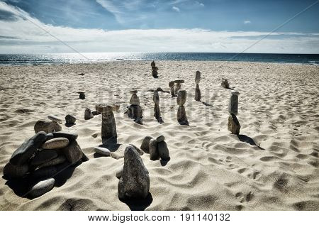 Tower of balancing stones on the beach, zen image with sea on background
