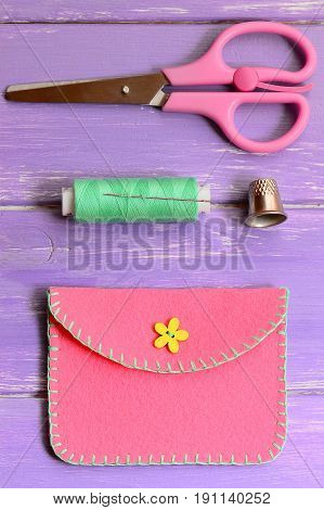 Cute pink felt purse with yellow flower wooden button. Scissors, thread, needle, thimble on a wooden table. Simple handmade crafts made of felt. Vertical photo. Top view