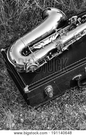 The saxophone lies on the black box on the sunset. Black-and-white photograph