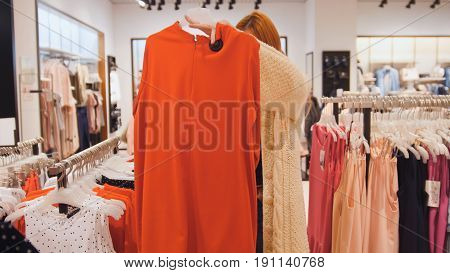 Shopping for woman. Beautiful girl looking at a red dress on a hanger