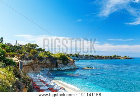 beach with white sand and clear blue water in Bay with sun beds and umbrellas, Crete, Greece