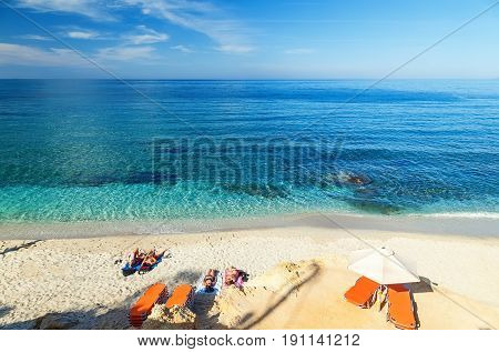young boys and girls on a beautiful beach with blue water and white sand, Crete, Greece