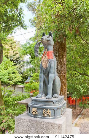 KYOTO JAPAN - MAY 17 2017: Statue of kitsune with rice sheaf in Fushimi Inari Taisha Shinto Shrine in Kyoto. Kitsune is a fox shapeshifter and a servant of Inari goddess
