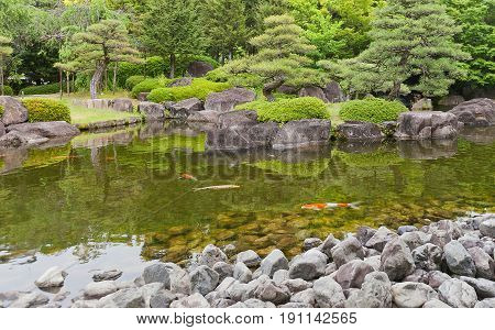 HIMEJI JAPAN - MAY 16 2017: Pond with carps in Kokoen Garden near Himeji castle Japan. Garden was laid out in 1992 to commemorate 100 anniversary of Himeji city