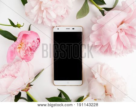 white phone with a clear screen on white background. peonies frame around. Flat lay.