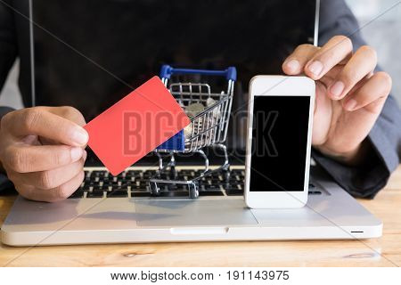 Male Showing A Credit Card And Mobile Smart Phone With Supermarket Cart Trolley On Laptop Computer F