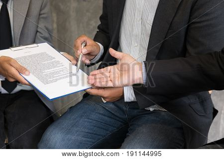 Businessman And Lawyer Negotiating A Contract, They Are Pointing On A Document And Discussing Togeth