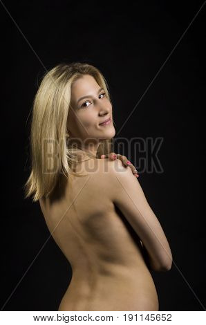 Portrait Of Nude Smiling Girl On A Dark Background.