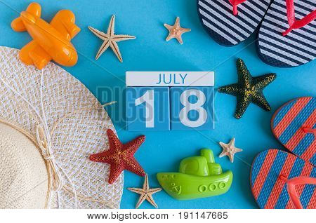 July 18th. Image of july 18 calendar with summer beach accessories and traveler outfit on background. Summer day, Vacation concept.
