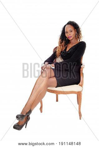 A beautiful young African American woman sitting in an old armchair relaxing isolated for white background.