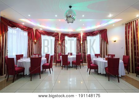 Empty banquet hall with three served tables, red chairs and drapes