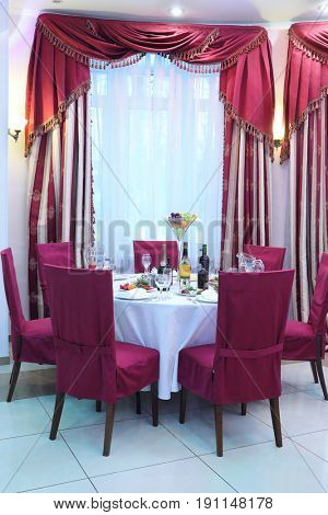 Beautiful round served table with red chairs and drapes in the banquet hall